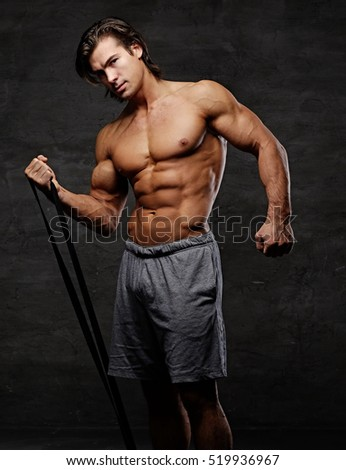 Shirtless athletic male doing biceps workouts with fitness trx straps on grey background in a studio.