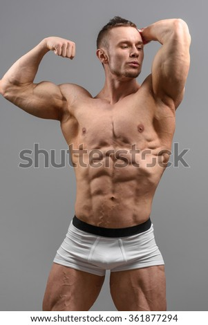 Shirtless athletic man looking at the side and posing over grey background in white underwear