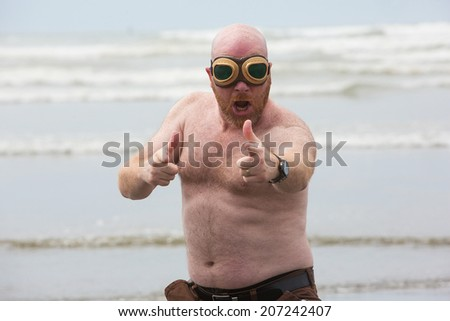 Shirtless bald man wearing aviator goggles at the beach