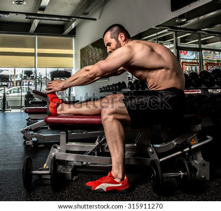 Shirtless bodybuilder doing exercises in a gym. - stock photo
