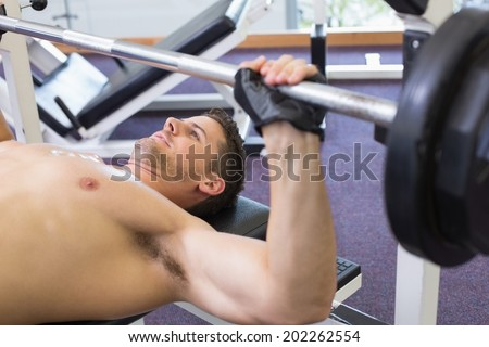 Shirtless bodybuilder lifting heavy barbell weight lying on bench at the gym