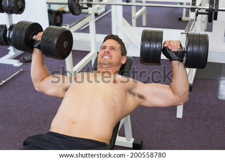 Shirtless bodybuilder lifting heavy dumbbells lying on bench at the gym