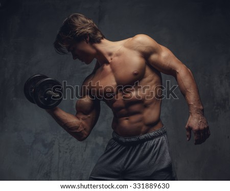 Shirtless bodybuilder showing his great body and holding dumbell.