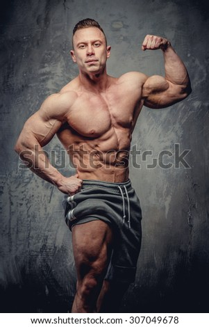 Shirtless bodybuilder showing his muscular torso and leg. Isolated on grey background.