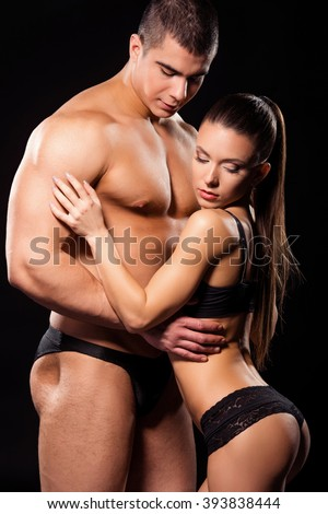 Shirtless bodybuilder with sexy model. Male fitness model touches girl.
