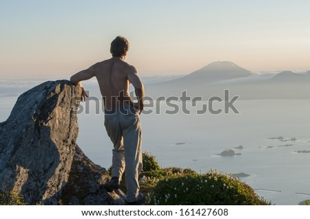 Shirtless Caucasian male hiker stands on top of Mount Verstovia gazing across Sitka Sound to Mount Edgecumbe during clear summer sunset - stock photo