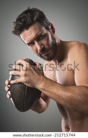 Shirtless confident football player holding ball and showing his muscular body