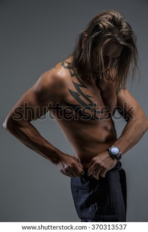 Shirtless fashionable male posing in deep shadow over grey wall.