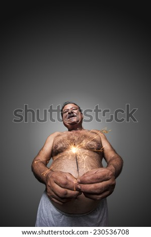 Shirtless Fat man holding a sparkles with hands. - stock photo