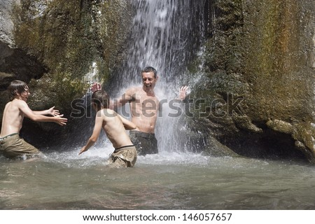 Shirtless father with two sons playing under waterfall