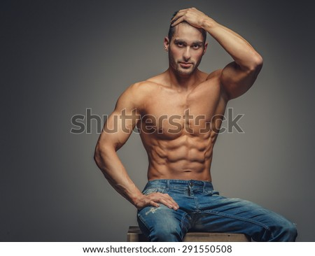 Shirtless guy in blue jeans sitting on podium. Isolated on grey background. - stock photo