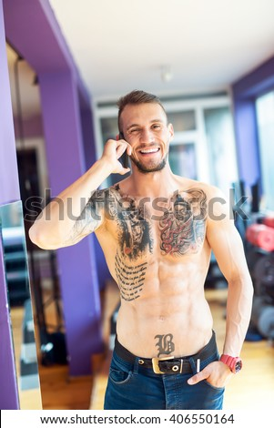 Shirtless handsome man talking on smart phone and smiling. - stock photo