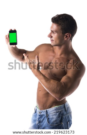 Shirtless handsome man with a muscular athletic body pointing to his mobile phone while displaying the blank green screen