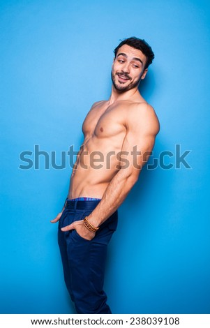 shirtless handsome man with beard looking back, on blue background - stock photo