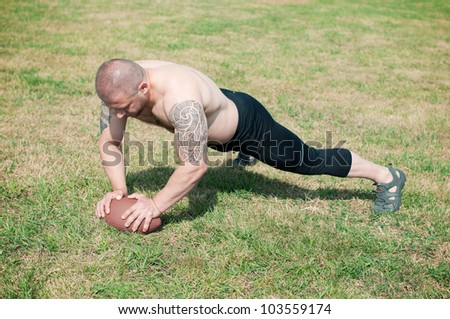 Shirtless male athlete doing push ups with american football ball - stock photo