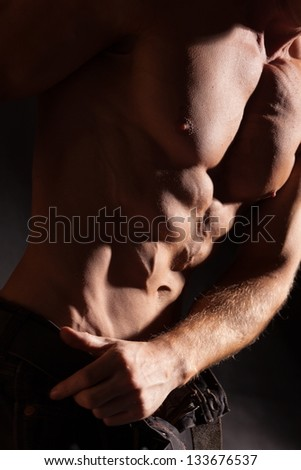 Shirtless male bodybuilder on a dark background