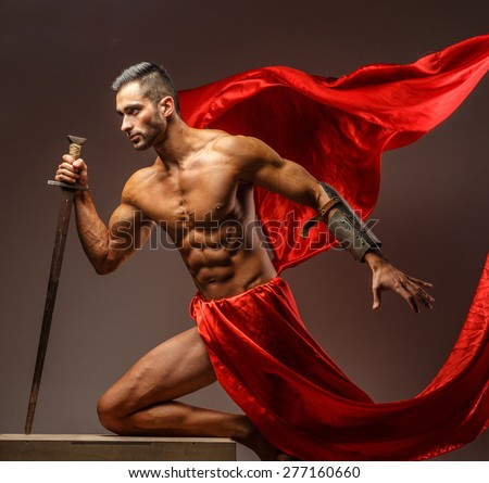 Shirtless male in roman armor with sword in motion. Red cloth on grey background - stock photo