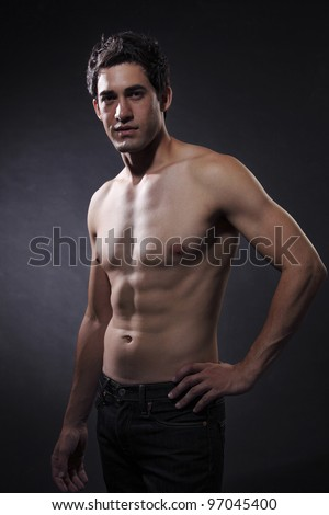 shirtless male model in jeans on the gray background