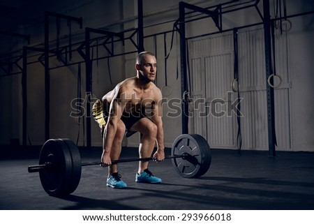 Shirtless man lifting barbells at gym - stock photo