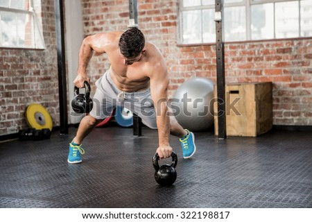 Shirtless man lifting kettlebell at the gym