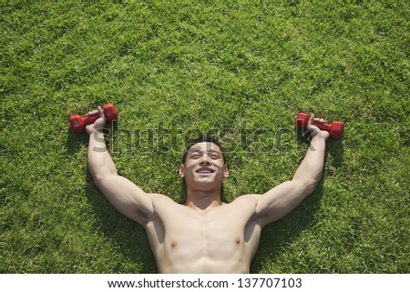 Shirtless Man Lying in Grass with Dumbbells in Beijing