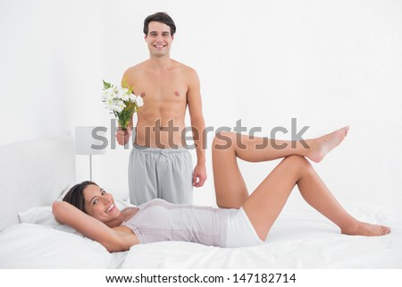 Shirtless man offering a bunch of flowers to his girlfriend in bed