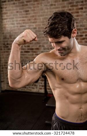 Shirtless man showing his biceps at the gym - stock photo