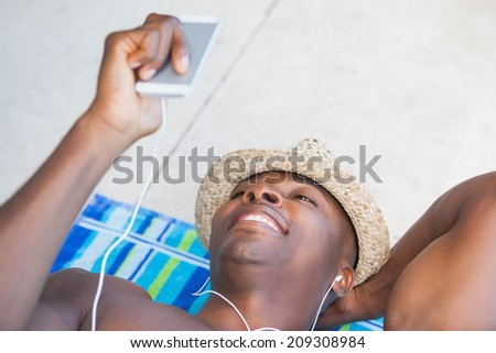Shirtless man smiling and listening to music on smartphone on a sunny day - stock photo