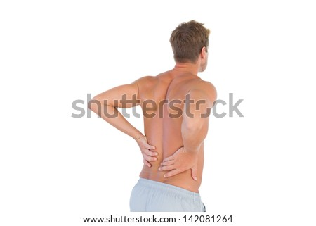 Shirtless man suffering from back pain on white background