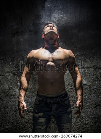 Shirtless Muscle Man Looking Up Into Bright Overhead Light Illuminating Him Like a Superhero - stock photo