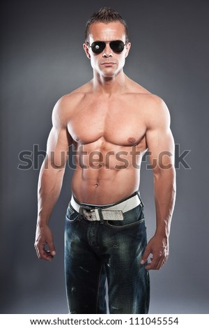 Shirtless muscled fitness man. Cool looking. Tough guy. Blue eyes. Blond short hair. Wearing black sunglasses. Tanned skin. Studio shot isolated on grey background. - stock photo