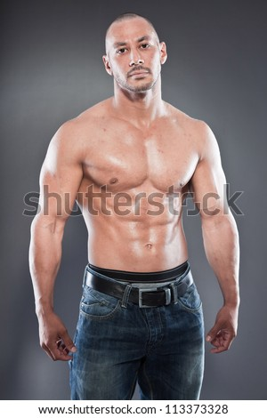 Shirtless muscled fitness man. Cool looking. Tough guy. Brown eyes. Bald. Tanned skin. Studio shot isolated on grey background. - stock photo