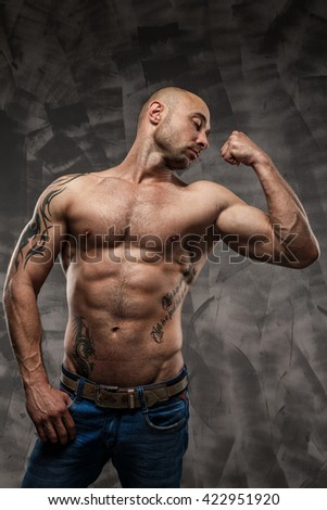Shirtless muscled fitness man. Cool looking. Tough guy. Brown eyes. Bald. Tanned skin. Studio shot on grey abstract background.