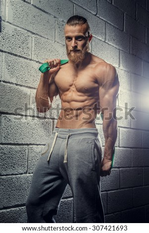 Shirtless muscular athlete guy holding weights and posing over grey wall from bricks.