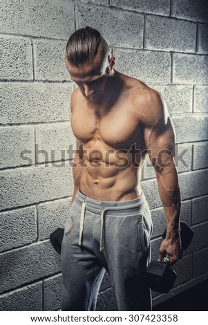 Shirtless muscular athlete guy holding weights and posing over grey wall from bricks. - stock photo