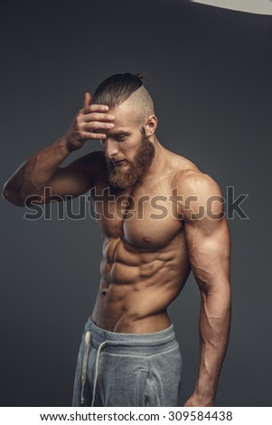 Shirtless muscular bodybuilder with beard posing over grey background.