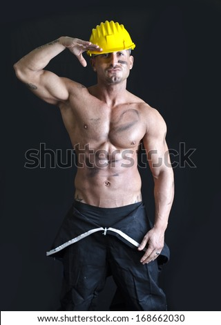 Shirtless muscular construction worker wearing coverall and hardhat with friendly expression