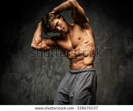 Shirtless muscular guy posing in studio and showing his great torso.