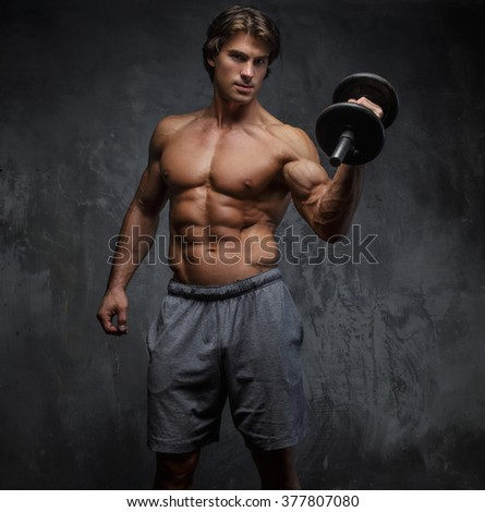 Shirtless muscular man holding a dumbbell.
