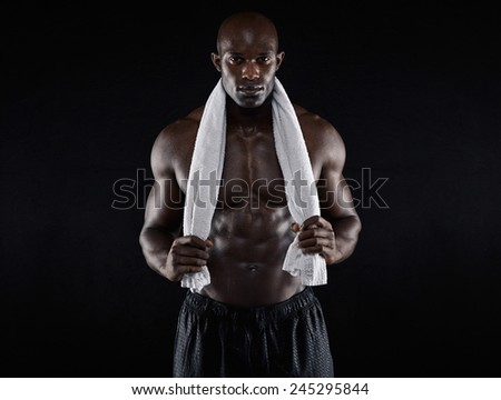 Shirtless muscular man holding towel looking at camera on black background. Fit young african man after workout. - stock photo