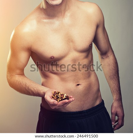 Shirtless muscular man holding various nuts. Closeup studio shot of unrecognizable fit slim young man holding almonds and walnuts in his hand. Square format, filter applied. - stock photo