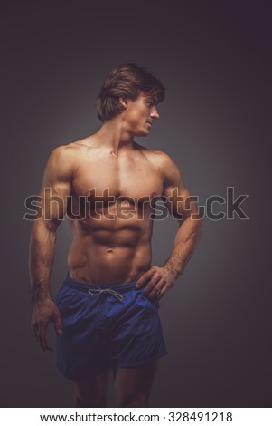 Shirtless muscular man in blue shorts posing over grey background. - stock photo