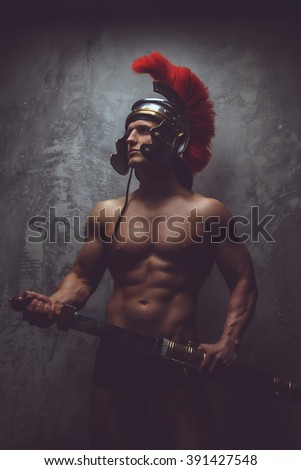 Shirtless muscular man in roman armour holds sword. - stock photo