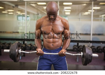 Shirtless muscular man lifting barbell in gym - stock photo