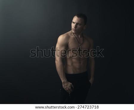 shirtless muscular man looks back - stock photo