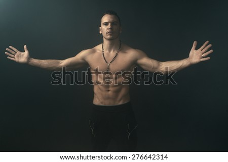 shirtless muscular man throws up his hands - stock photo