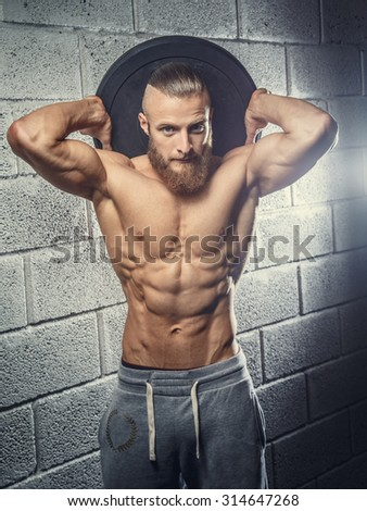 Shirtless muscular man with beard holding disk weight behind his head. Grey wall from bricks background.