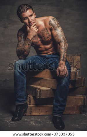 Shirtless muscular man with tattooes on his body sitting on wooden boxes.