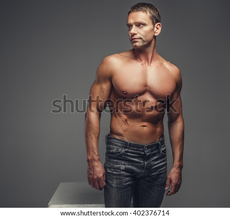 Shirtless muscular middle age man in a jeans posing in a studio on a grey background.