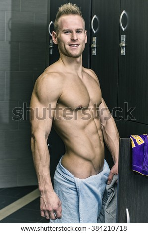 Shirtless muscular young male athlete in gym dressing room - stock photo